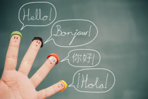 Four smiley fingers on a blackboard saying hello in English, French, Chinese and Spanish.